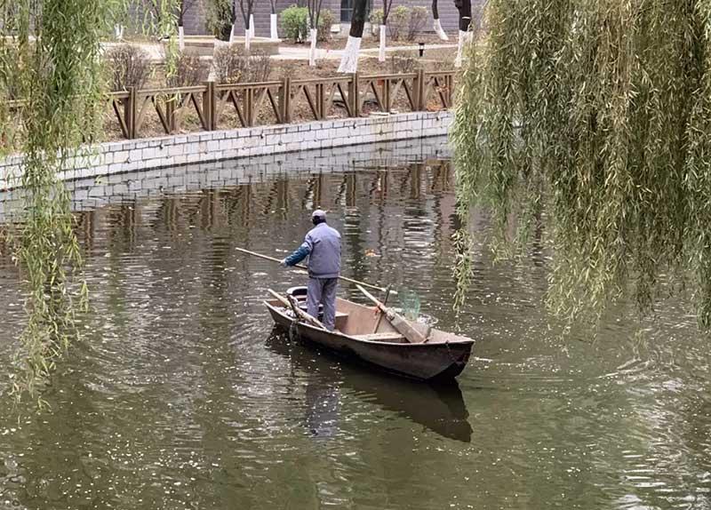 打捞落叶的小船在水中艰难的工作